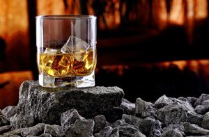 Glass of whiskey and ice.Creative photo glass of whiskey on stone with sunset background.Copy space.Advertising shot