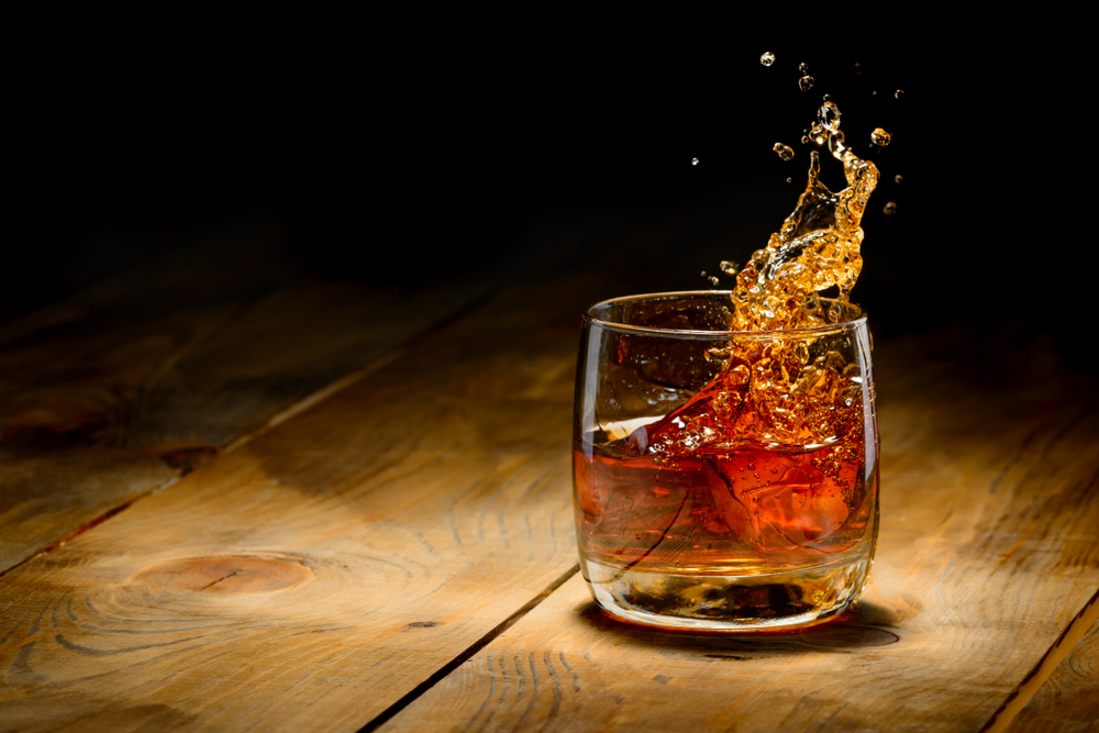 Whiskey splash in glass on a wooden table.